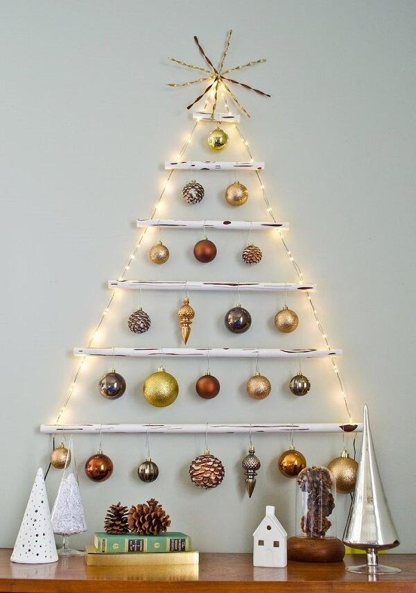 Árvore de Natal na parede feita com pisca pisca e bolinhas natalinas
