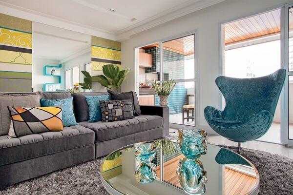 Sala de estar com sofá suede cinza e poltrona em tom azul turquesa