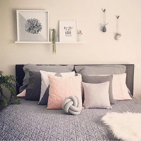A almofada de nó cinza complementa a decoração do quarto de casal