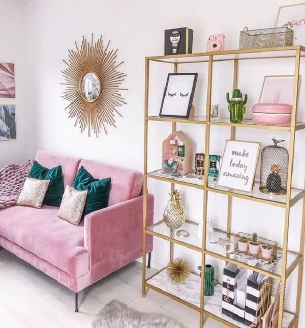 Sala de estar com prateleira em tom dourado e sofá rosa