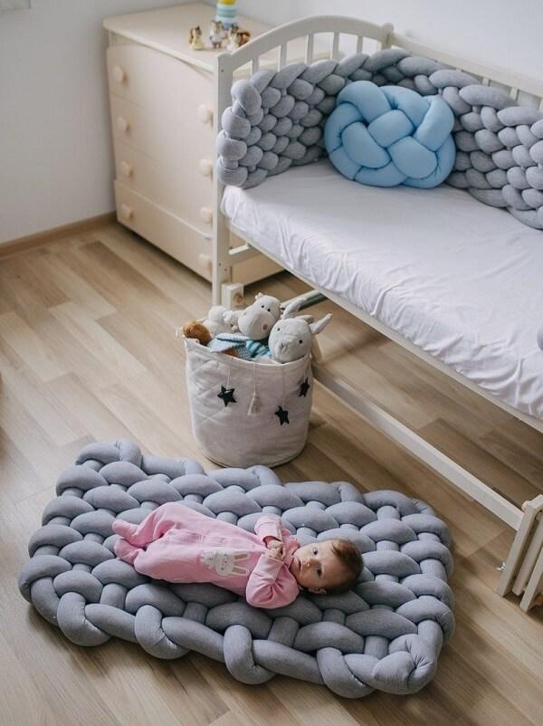 A almofada de nó com manta cinza complementa a decoração do quarto de bebê