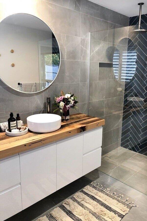 banheiro cinza e branco decorado com espelho redondo e bancada de madeira Foto Creative Remodeling