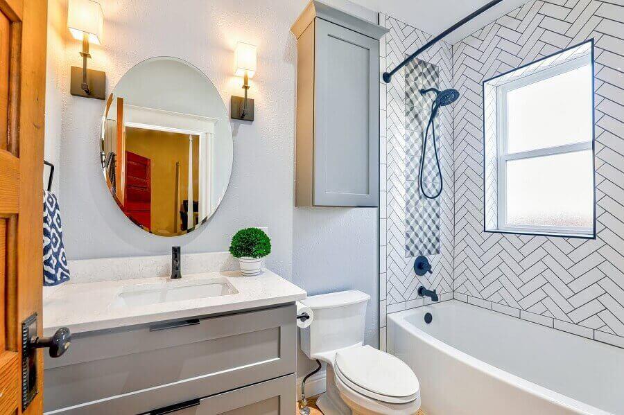 banheiro com banheira pequena decorado com espelho redondo