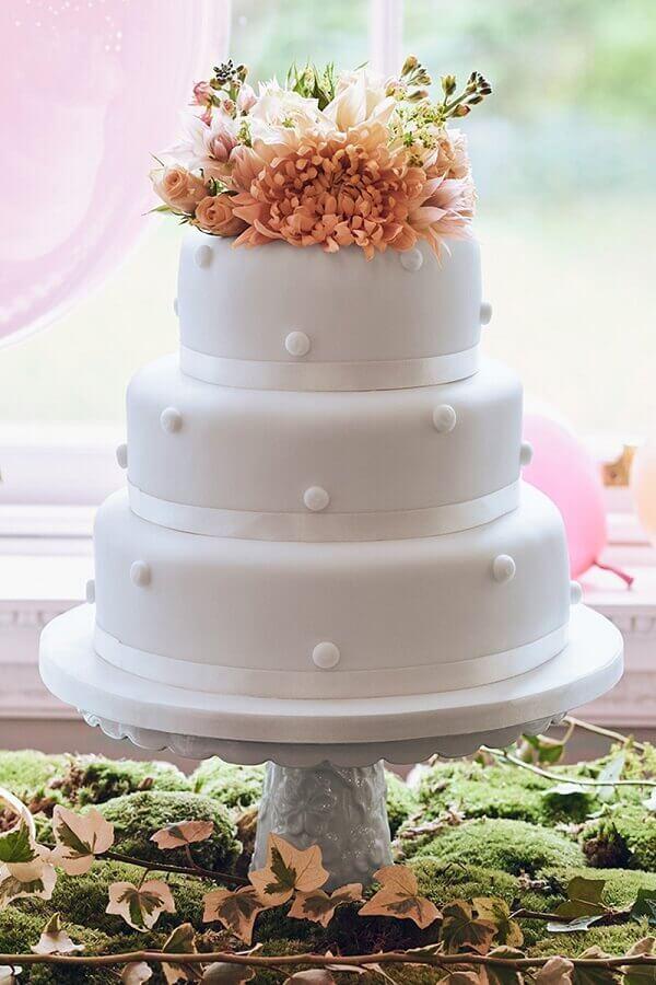 bolo fake de casamento com flores no topo Foto Assetproject