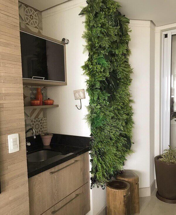 Traga um pouco de verde para a varanda incluindo um jardim vertical com flores artificiais na parede