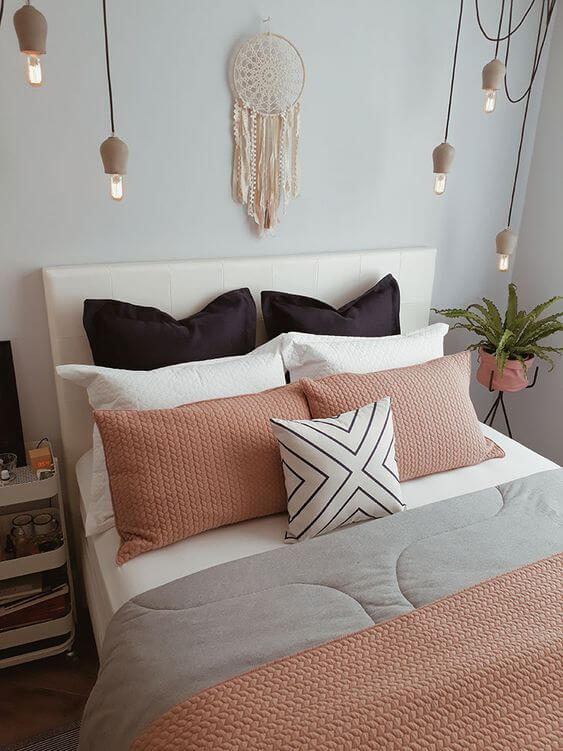 Cama arrumada com travesseiros e almofadas combinando com o quarto
