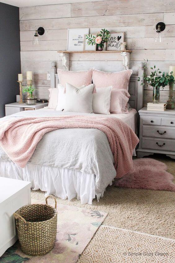 Cama arrumada com manta rose e travesseiros branco