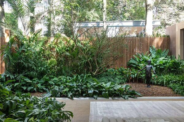 Jardim residencial com cerca de bambu ao fundo
