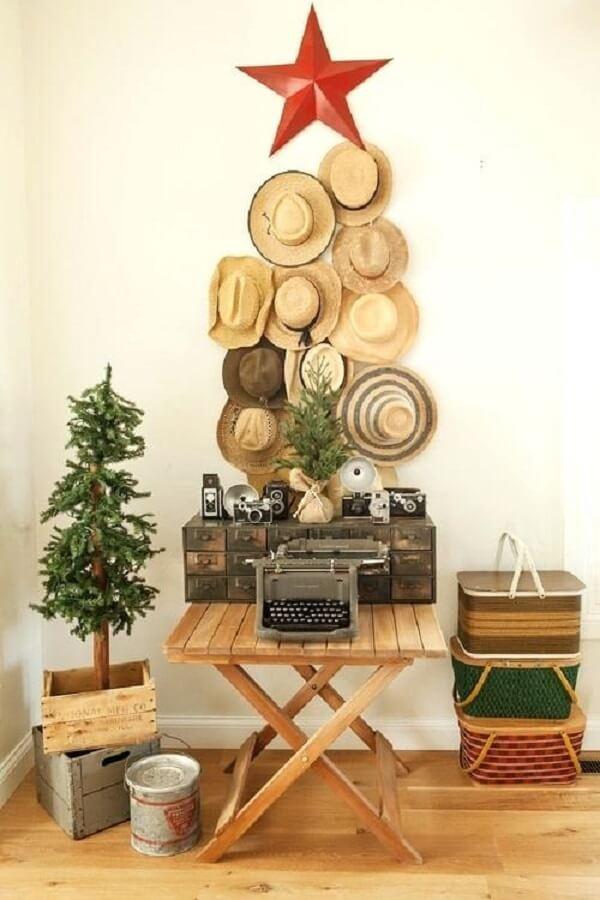 Árvore de Natal na parede feita com chapéus de palha