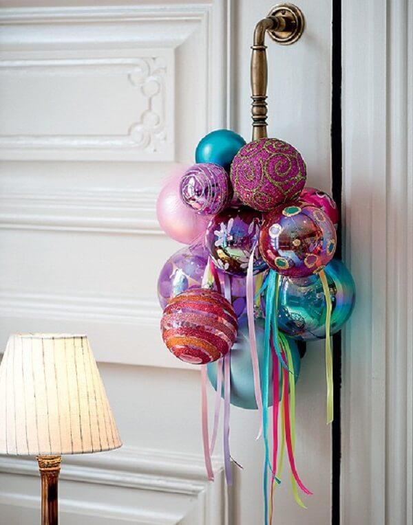 Enfeite de natal para porta feito com bolas coloridas e posicionado na maçaneta da porta