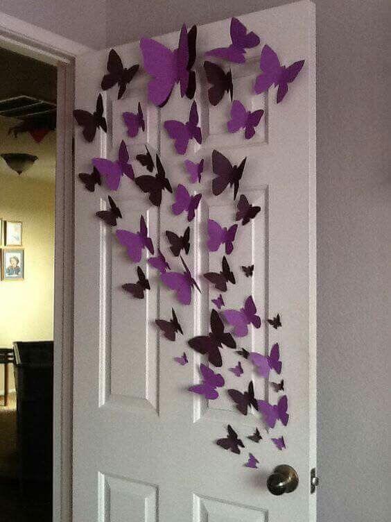 Borboletas de papel roxo na porta do quarto infantil