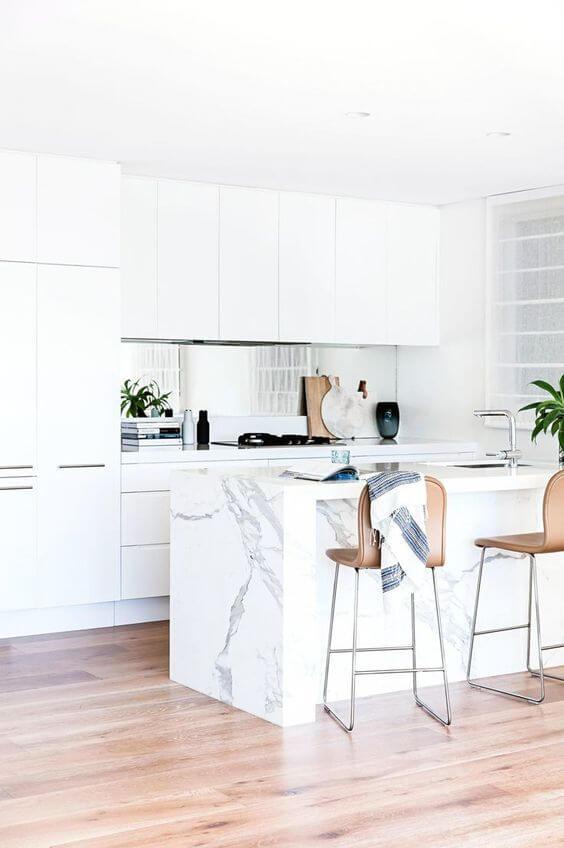 Cozinha branca com bancada marmorizada e detalhes em rose
