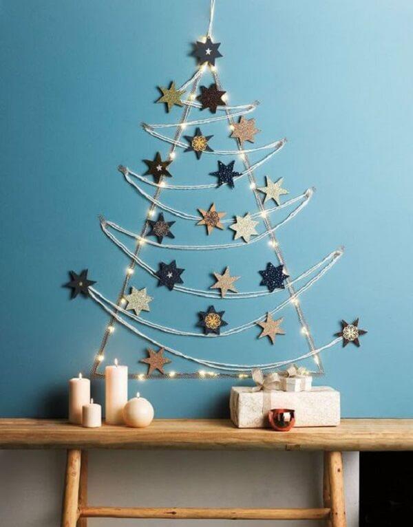 Árvore de Natal na parede feita com estrelas e pisca pisca