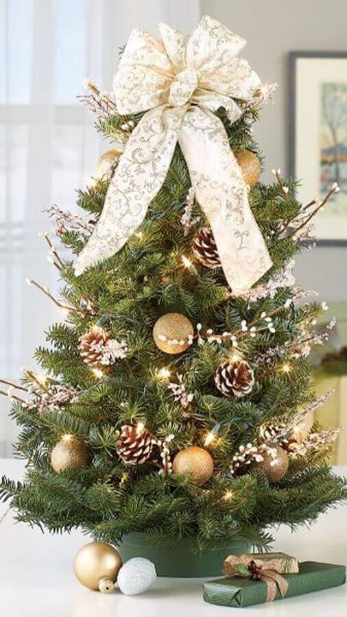 decoração de árvore de Natal pequena com pinhas e bolas douradas Foto Cultura Colectiva
