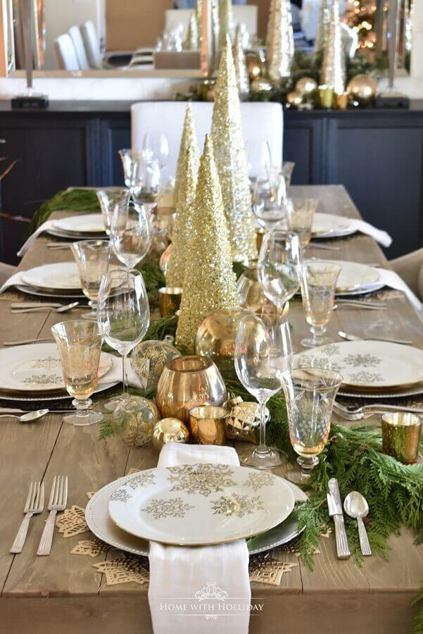 decoração mesa réveillon com folhagens e pequenos pinheiros dourados Foto Home With Holliday