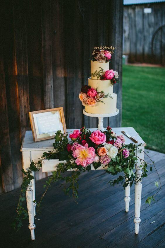Decoração de casamento simples com bolo e flores em tons de rosa