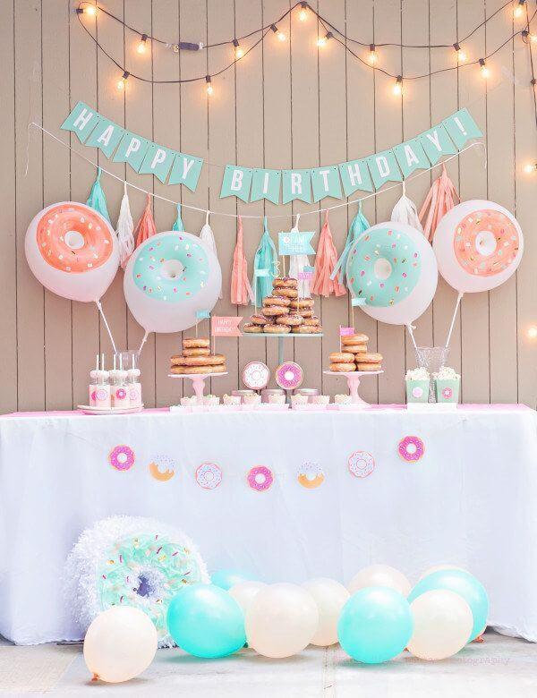 Decoração de festa de aniversário simples com muitos donuts no lugar do bolo