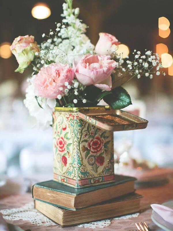 Decoração de festa simples com livros e flores na mesa