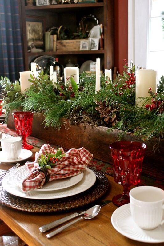 Centro de mesa natal com plantas e velas e taças vermelhas