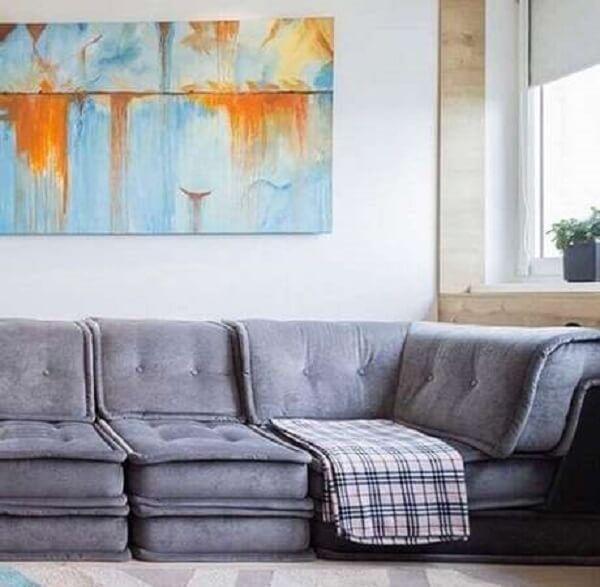 Sala de estar com sofá suede em tom cinza e manta estampada