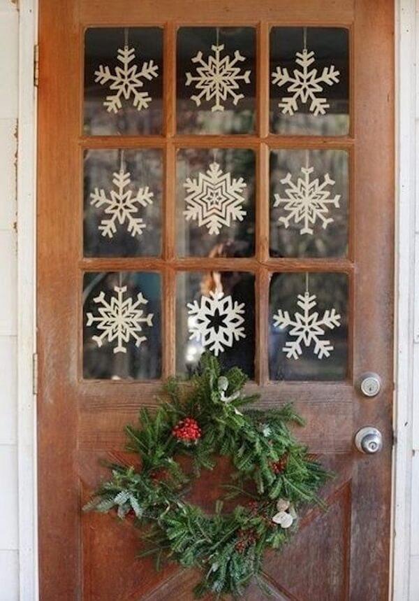 Enfeite de natal para porta feito com ramos e flocos de neve