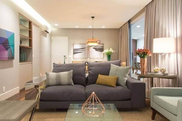 Sala de estar com sofá suede dois lugares e mesa de centro de vidro