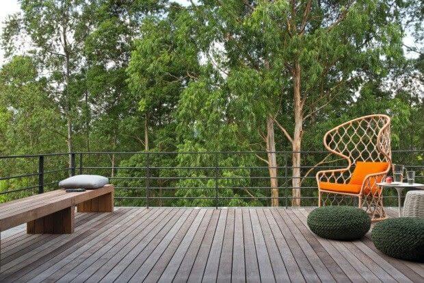 Decoração de terraço com cadeira laranja e puff de crochê verde