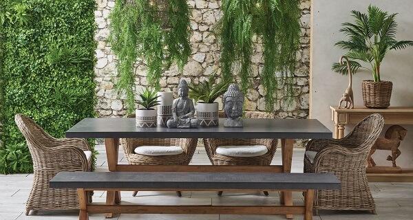 Varanda espaçosa com parede de pedra, vasos suspensos e jardim vertical com plantas artificiais