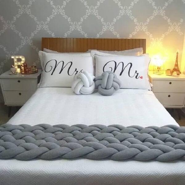 As almofadas de nó em tons branco e cinza se misturam com a decoração do quarto de casal