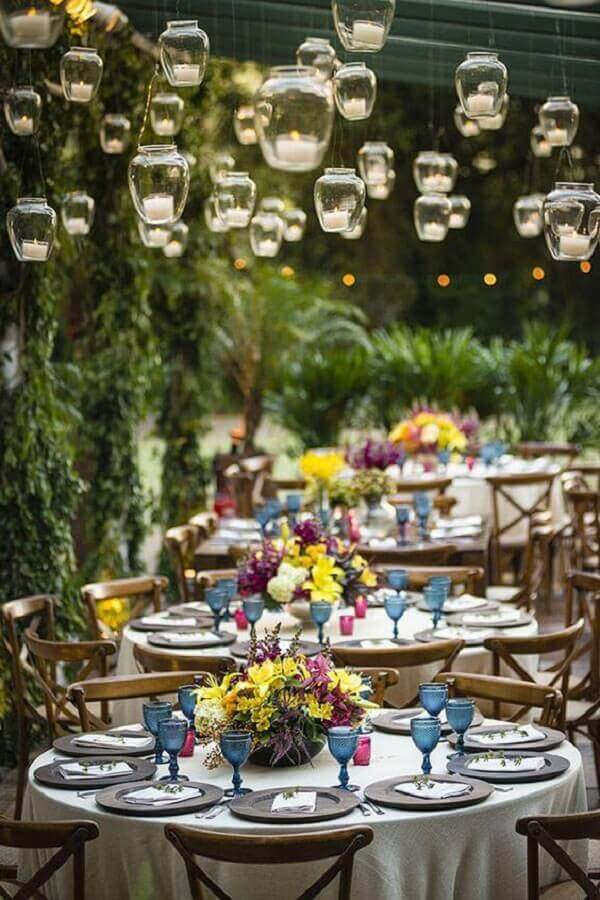 festa de casamento no campo decorada com velas suspensas e arranjo de flores coloridas Foto Luxury Wedding