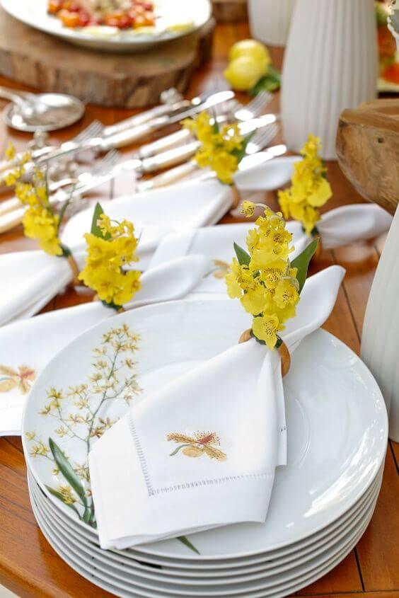 Guardanapo de tecido branco e bordado com flores amarelas no anel
