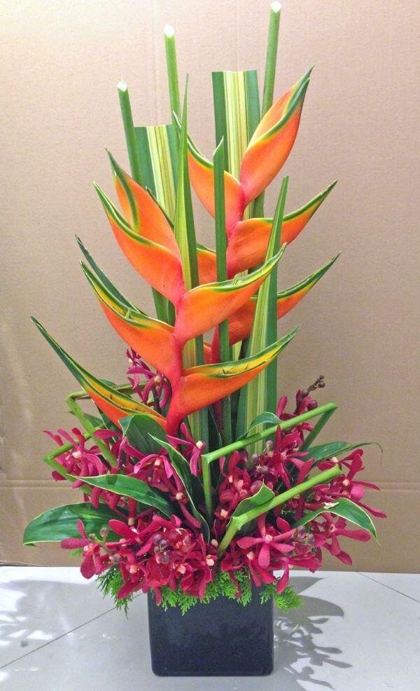 Helicônia laranja com plantas fucsia