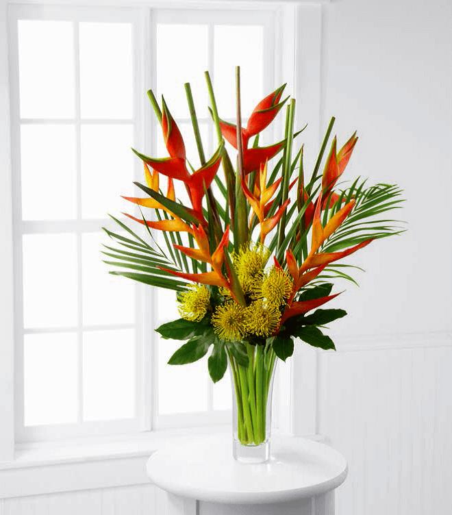 Arranjo com helicônia e plantas no vaso de vidro