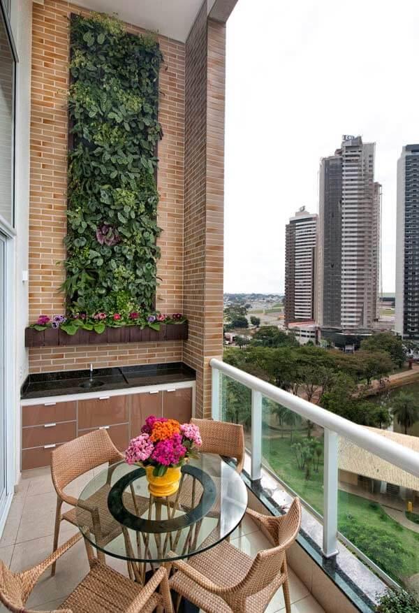 Varanda com pé direto alto e parede revestida com jardim vertical artificial
