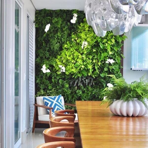 Sala de jantar com móveis de madeira e parede revestida com jardim vertical artificial