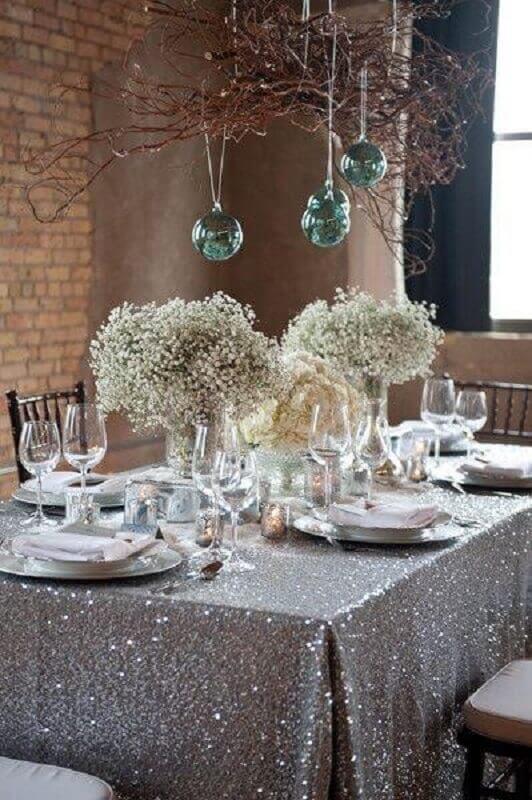 mesa de ano novo decorada com toalha prata e arranjo simples com flores Foto Pinterest