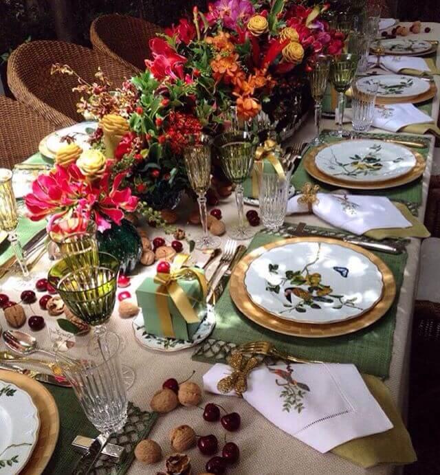 Mesa decorada com muitas flores e aparelho de jantar delicado