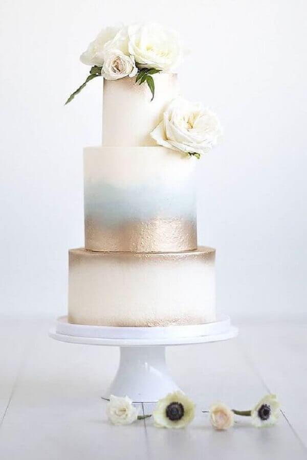 modelo moderno de bolo de casamento com acabamento dourado e rosas brancas Foto ELLE Decoration