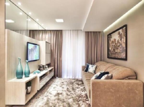 Sala de estar com sofá suede e parede de espelho
