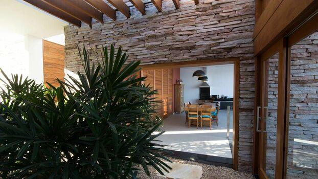 parede de pedra - pergolado de madeira e parede de pedra com junta seca