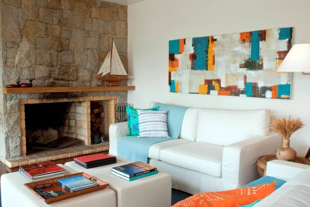 parede de pedra - sala de estar com lareira e detalhes coloridos