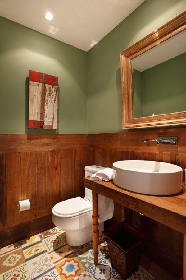 parede verde musgo para banheiro com revestimento de madeira e piso hidráulico  Foto Revest Acabamentos