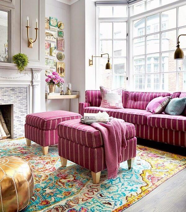 Sala de estar com sofá rosa e puffs listrados