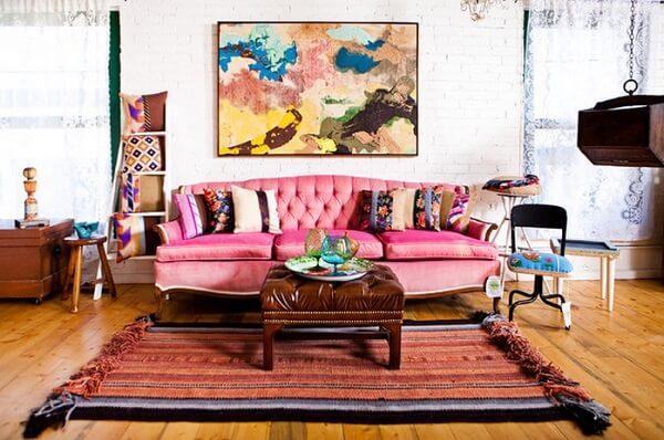 Sala de estar com sofá rosa, almofadas estampadas e quadro abstrato