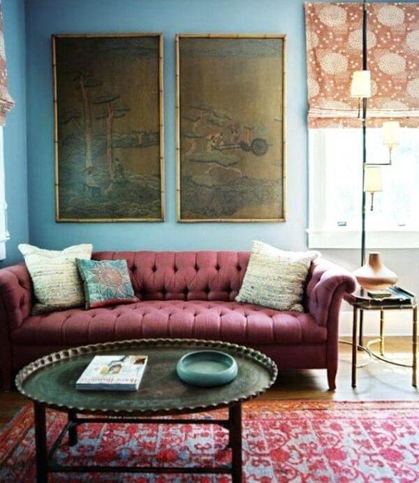 Sala de estar com sofá rosa feito com acabamento em capitonê