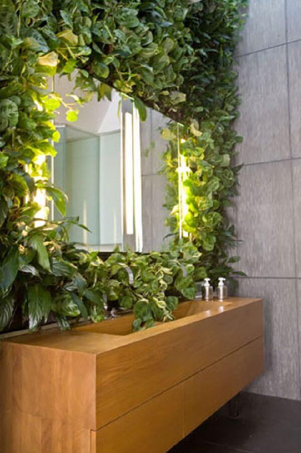 O jardim vertical artificial serviu de moldura para o espelho do banheiro
