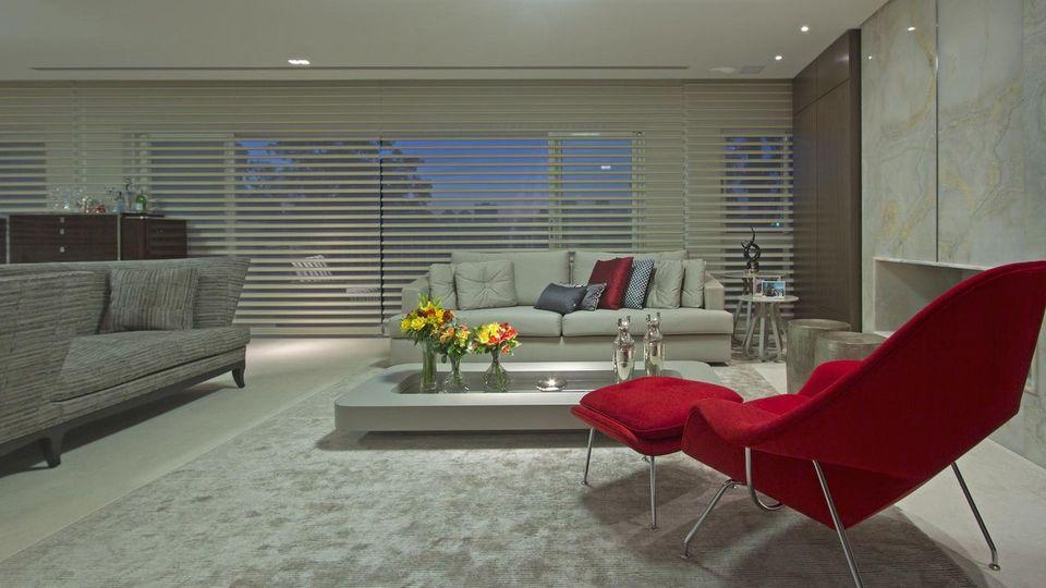 poltrona vermelha - sala de estar com tapete cinza e tapete vermelho