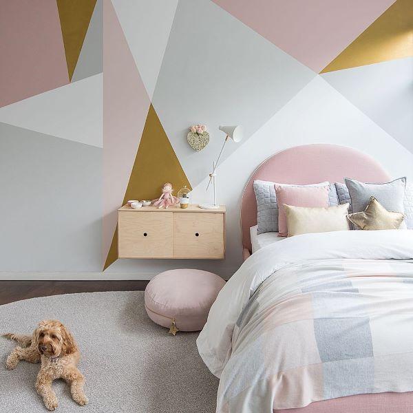 Quarto rosa com papel de parede geométrico