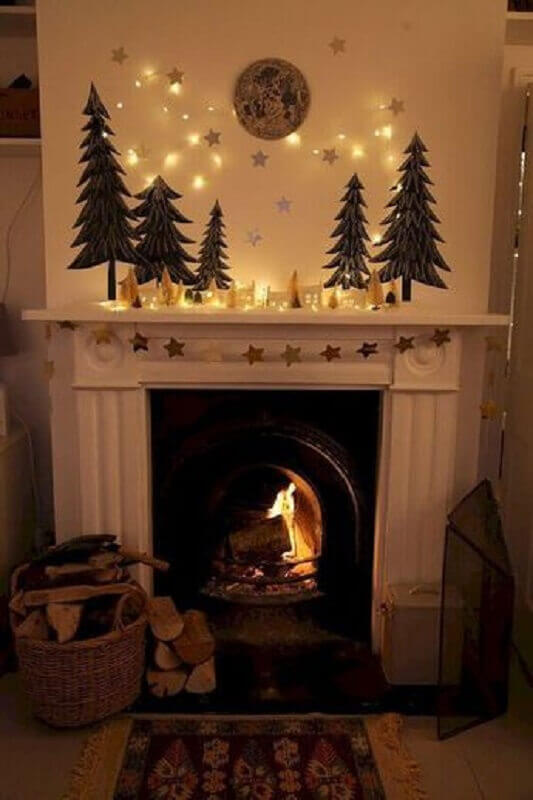 Living room with fireplace with simple Christmas decoration with gold stars and small pine trees Foto Pinterest