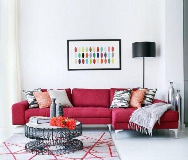 Sala de estar com sofá suede em tom vermelho e almofadas estampadas